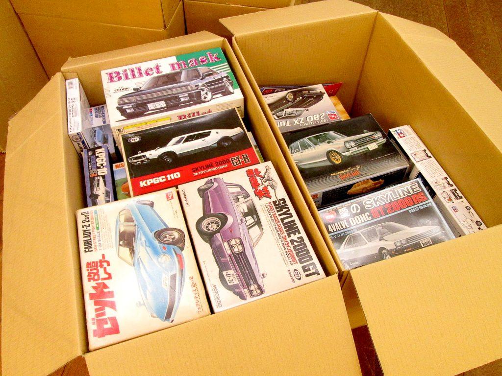 ダンボールに入った乗用車やレーシングカーのプラモデル